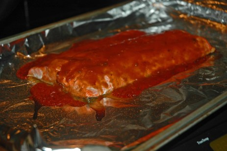 Baking salmon with a little bit of BBQ sauce on it.